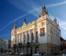 """Theater des Westens / Theater des Westens (Западный театр) находиться в Берлине, здание построено в 1895/96 годах в стиле позднего историзма (необарокко). Театр был открыт спектаклем-сказкой """"Тысяча и одна ночь"""".  В 1898 году театр был преобразован в оперу, а в 1908 в оперетту.  В 1924 году театр был закрыт из-за экономических проблем.  В 1933 нацисты открыли театр снова в рамках нацисткой государственной программы """"Kraft durch Freude"""" (Сила через радость)  для поднятия духа немецкого населения и переименовали его в """"Народную оперу"""". В 1944 здание было сильно повреждено бомбежкой. Однако уже в 1945 после окончания войны восстановлено и с этого момента по 1961 театр был главной оперной трибуной Берлина. Пока не была восстановлена """"Немецкая опера"""", разрушенный во время войны оперенный театр на улице Бисмарка. Сейчас """"Theater des Westens"""" используется в основном для показа оперетт и мюзиклов.  На стене можно разглядеть плакат """"Tanz der Vampire"""" (Танцы вампиров) – мюзикл римейк фильма Романа Поланского """"The Fearless Vampire Killers"""" (Бесстрашные убийцы вампиров) снятого в 1967 году. Цена билета: 56 - 80 евро."""